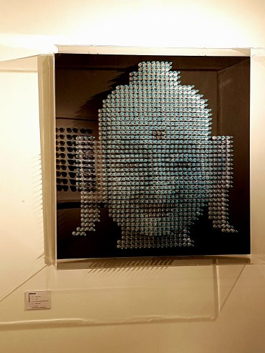 Smiling Buddha wall sculpture by Anthony Moman in Woolff Gallery
