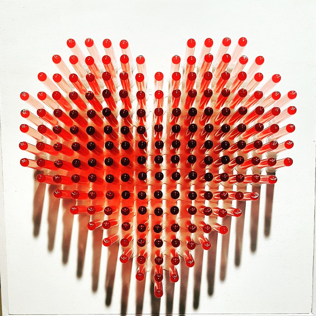 Red heart sculpture made from test tubes filled with liq