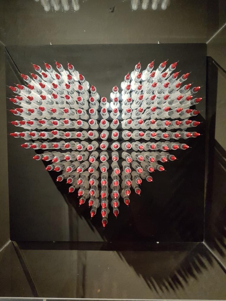 Love is the drug heart sculpture syringes